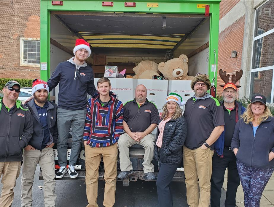 The Servpro gangs along with Angel standing in front of a Servpro box truck full of toys being delivered to the Brrr Bash
