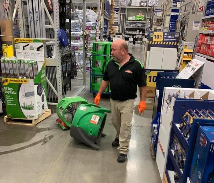 This is a picture of one of our techs in a Lowes cleaning up water damage.  he is in the flooring section of Lowes.
