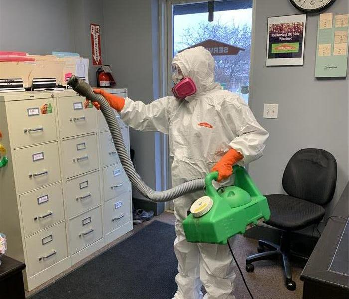 Joanne, one of our owners, in full PPE holding a macromist mister and doing a preventative disinfecting of the office.