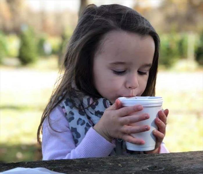 small child is sitting at a picnic table outside sipping hot chocolate from a Styrofoam cup.
