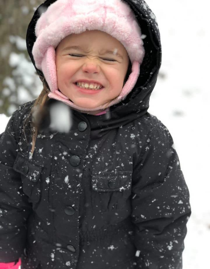 Jojo smiling big with a snow hat and coat on and snow all around her