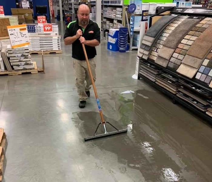 SERVPRO Crew Chief mopping floors at a local store